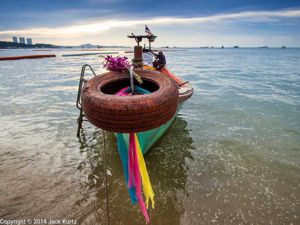 """26 SEPTEMBER 2014 - PATTAYA, CHONBURI, THAILAND: A boat moored on Pataya Beach. Pataya, a beach resort about two hours from Bangkok, has wrestled with a reputation of having a high crime rate and being a haven for sex tourism. After the coup in May, the military government cracked down on other Thai beach resorts, notably Phuket and Hua Hin, putting military officers in charge of law enforcement and cleaning up unlicensed businesses that encroached on beaches. Pattaya city officials have launched their own crackdown and clean up in order to prevent a military crackdown. City officials have vowed to remake Pattaya as a """"family friendly"""" destination. City police and tourist police now patrol """"Walking Street,"""" Pattaya's notorious red light district, and officials are cracking down on unlicensed businesses on the beach.     PHOTO BY JACK KURTZ"""
