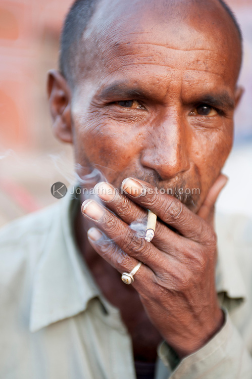 Tight shot of a  man smoking a cigarette and looking at the camera.