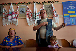 Ljudmila Kashpirovska, listens as Olexander Chuzha voices his concerns about the dangers of high voltage power lines in close proximity to his home, Bila Tserkva, June 14, 2011. His daughter Katerina Cherednichenko, 3, has a candy while he looks for legal advice at the village community center.  More than half of the worldÕs population, four billion people, live outside the rule of law, with no effective title to property, access to courts or redress for official abuse. The Open Society Justice Initiative is involved in building capacity and developing pilot programs through the use of community-based advocates and paralegals in Sierra Leone, Ukraine and Indonesia. The pilot programs, which combine education with grassroots tools to provide concrete solutions to instances of injustice, help give poor people some measure of control over their lives.