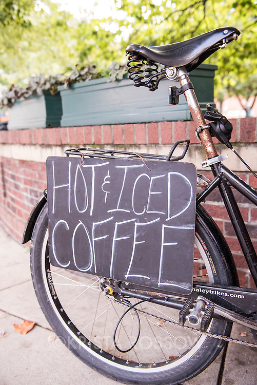 """Sign for """"hot and iced coffee"""" at the Coffee Pedlar, a mobile bicycle coffee cart that he often parks at Pritchard Park in downtown Asheville, North Carolina."""