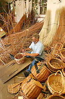 craftsman weaving a basket from willow