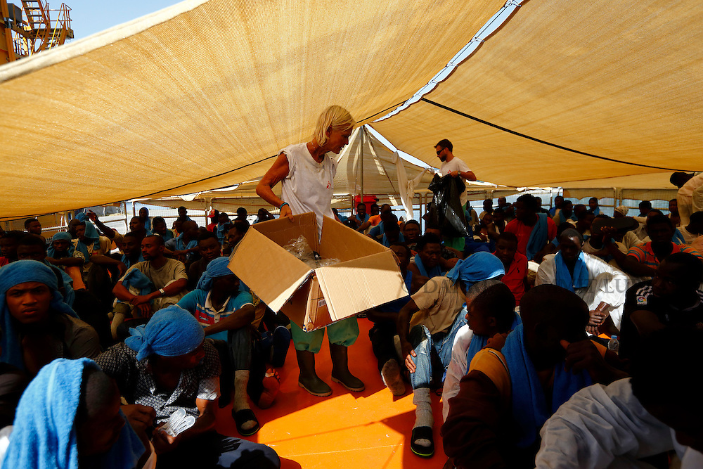 A Medecins san Frontiere (MSF) nurse distributes sandals to Sub-Saharan migrants sitting on the deck of the Migrant Offshore Aid Station (MOAS) ship MV Phoenix in Vibo Valentia, Italy, July 31, 2015.  195 migrants who were rescued off Libya on Wednesday arrived in Italy on Friday afternoon. The Phoenix, manned by personnel from international non-governmental organisations MSF and MOAS, is the first privately funded vessel to operate in the Mediterranean.<br /> REUTERS/Darrin Zammit Lupi <br /> MALTA OUT. NO COMMERCIAL OR EDITORIAL SALES IN MALTA