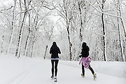 Two women running in a Snow covered Mont Royal Park in Winter, Parc du Mont Royal, Montreal, Quebec, Canada