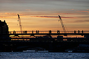 People crossing the river Thames on the Millennium Bridge at sunset. Silhouetted against the golden sky in the evening light.
