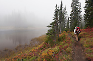 A man hikes along trail along foggy Junction Lake in the Indian Heaven Wilderness in the Gifford Pinchot National Forest - Cascade Mountain Range of Washington state in autumn.