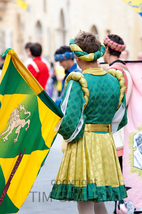 Contrada young men in livery costumes at traditional parade in Asciano, inTuscany, Italy