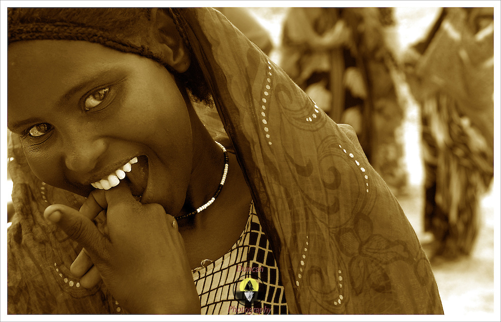 Ahadi Mohammed, 13, is shy but was willing to be photographed.  In order to make this picture the photographer befriended a young man who asked the Ahadi if the photographer could make the picture. She agreed. Djiboutian women are very shy and deferent to men in most cases. It is considered rude to look at women and speaking to them is also considered inappropriate. <br />