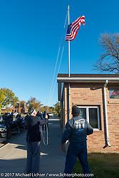 Commander Bob Wegner of the Groton American Legion Post #39 and Groton Mayor Scott Hanlon raise a flag during a stop in Groton, SD for a flag raising ceremony during the USS South Dakota submarine flag relay across South Dakota. USA. Sunday October 8, 2017. Photography ©2017 Michael Lichter.