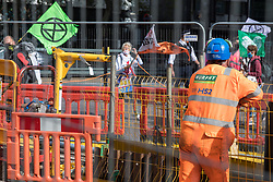 Activists from HS2 Rebellion, an umbrella campaign group comprising longstanding campaigners against the HS2 high-speed rail link as well as Extinction Rebellion activists, march past HS2 workers with the handmade Boris the Bank Engine to a protest rally in Parliament Square on 4 September 2020 in London, United Kingdom. The rally, and a later protest action at the Department of Transport during which activists glued themselves to the doors and pavement outside and sprayed fake blood around the entrance, coincided with an announcement by HS2 Ltd that construction of the controversial £106bn high-speed rail link will now commence.