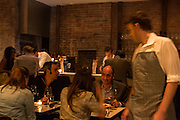 New York, NY, Sept. 30, 2013. Grant Reynolds, wine director at Charlie Bird. Patrons in the dining room.