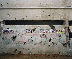 Martyr posters and shrapnel marks line the wall of a destroyed home in Beit Hanoun, Gaza Strip, Palestinian Territories, Nov. 24, 2006. According to Human Rights Watch, since September 2005, Israel has fired about 15,000 rounds at Gaza while Palestinian militants have fired around 1,700 back.