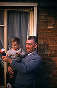 A 1960s father holds his young one year-old son, showing the childs favourite toy outside the family home, in March 1961, in Westcliff, Southend, Essex, England.