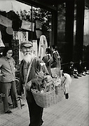 C012-36_Tom Hutchins_Old bamboo-goods pedlar in front of Department Store, Sunday, Wang Fu Chin, Peking, 1956 A2.tif