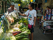 09 MARCH 2016 - BANGKOK, THAILAND:  A man buys produce from a door to door vendor in the Pom Mahakan community in Bangkok. The community of about 50 families was once known as the cockfighting center of Bangkok. Gambling, is now prohibited by the military government and cockfighting is not as popular as it once was. Cockfights are still staged in clandestine pits in Bangkok but outside of Bangkok cockfights are common.    PHOTO BY JACK KURTZ