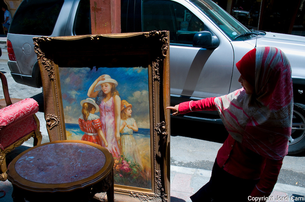 BEIRUT,LEBANON - JUNE 2009 :  A  Muslim girl looks a paint which show  a  west style life  in a  antiques shop at  the Shiite district of Basta. Beirut. Lebanon.  06/12/2009 ( Photo by Jordi Cami)