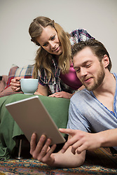Couple using digital tablet in living room and smiling, Munich, Bavaria, Germany