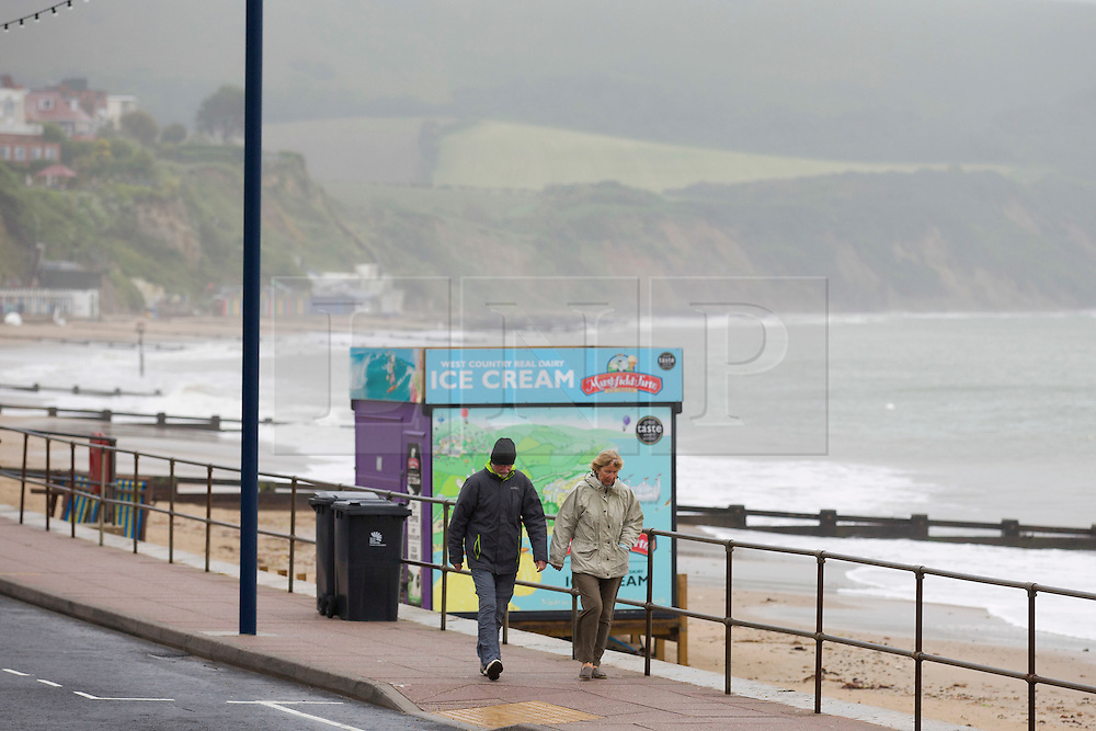 © London News Pictures. 02/06/2015. United Kingdom, Swanage. Two people wrapped up for a walk. Grey skies cover the sky over a windy seafront at Swanage, Dorset, on June 2, 2015. Photo credit: LNP