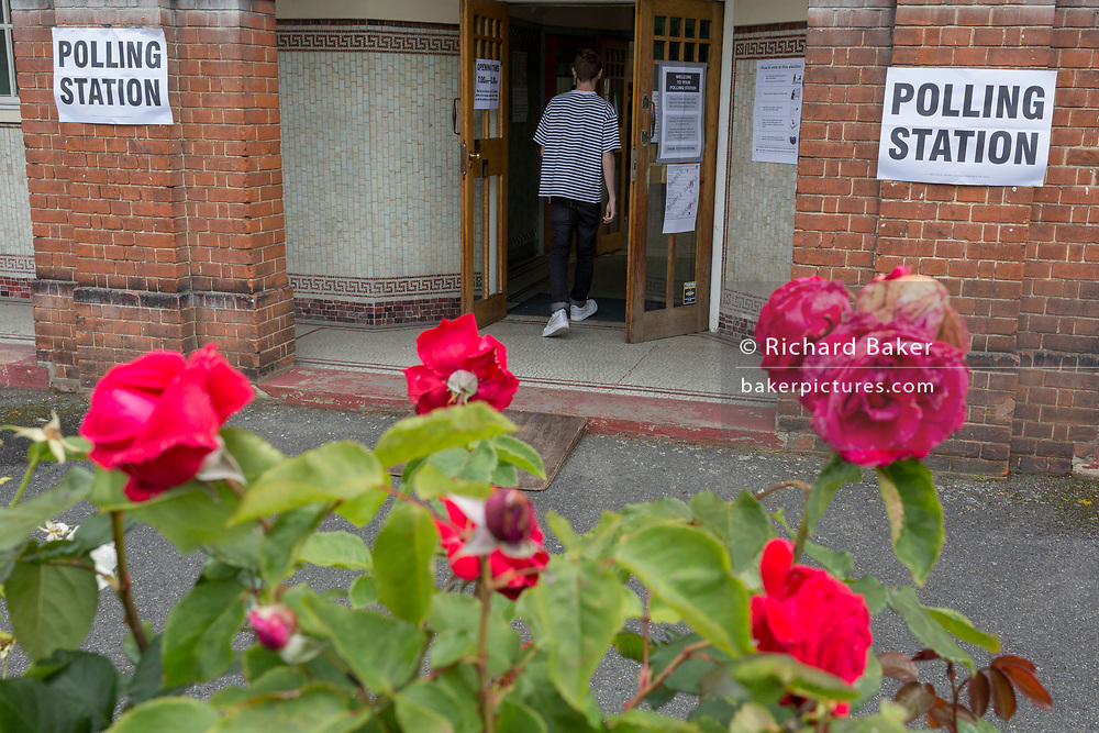 Seen through (the Labour Party symbol) red roses, a young voter arrives at the polling station on the morning of the UK 2017 general elections outside St. Saviour's Parish Hall in Herne Hill, Lambeth, on 8th June 2017, in London, England.