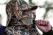 Vance Fielder in full camo gear calls for ducks while hunting in Shamrock, Oklahoma