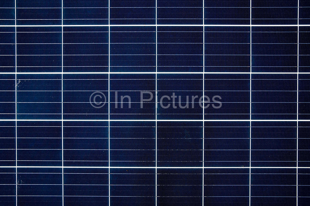 Close-up of a photovoltaic solar energy panel with reflection of the sun. This panel, or module, is made up of photovoltaic PV cells. PV cells convert sunlight into electrical energy in Hackney, London United Kingdom. Photovoltaic panels are an economical, efficient way to produce electricity that does not pollute or contribute to global warming. Solar photo voltaic PV panels on the roof of Hackney council estate Bannister House, the first community solar installation on a estate in Hackney, London United Kingdom.  Bannister House was Hackney's first community solar installation, Banister House Solar, has been developed by Re-powering London in partnership with local estate residents and Hackney Council, and delivered using funds raised through a community share offer. The 102kWp solar array generates up to 82,000kWh of energy annually, saving 50,000kg of CO2 emissions. In addition, a portion of the revenue generated through the government's Feed-in Tariff and sale of energy over the 20-year life of the project will generate over £28,000 for the Banister House Solar community fund. Hackney, London.