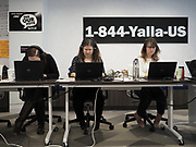 The Spanish and English language Election Protection hotline numbers of 1-844-YALLA-US and 866-OUR-VOTE are posted behind volunteers answering calls from concerned voters on how and where to cast their ballots.