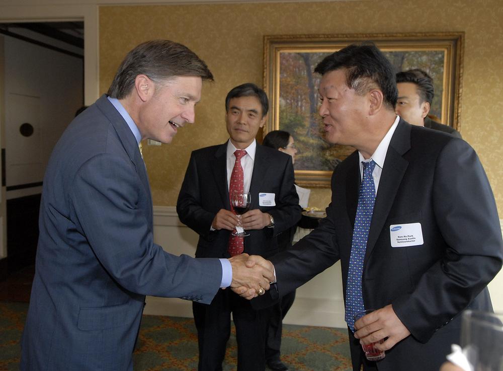 Austin, Texas May 16, 2006:  Austin Mayor Will Wynn (left) greets Korean businessmen at a Samsung Semiconductor appreciation event at a local club. ©Bob Daemmrich /