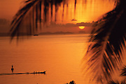 A view of the sun setting on the horizon through palm trees that line the ocean in Thailand