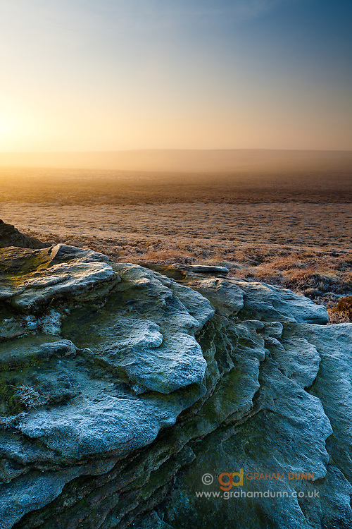 Ox Stones. Heavy frost accentuates the ragged curves on this gritstone tor on Burbage Moor. Peak District.