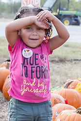 Girl in Halloween pumpkin patch, Mitchell Lake Audubon Center, San Antonio, Texas, USA.