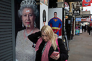 A woman walks past images of Queen Elizabeth II, a guardsman and Superman, on 3rd February 2017, in London, England.