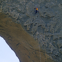 Sam Lightner (MR) rappels on huge Shipton's Arch, one of earth's biggest, in the arid Kara Tagh Mountains near Kashgar and the Taklimakan Desert.