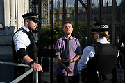 Demonstration in Parliament Square called by Extinction Rebellion to protest the government's inaction on climate change and calling for a mass rebellion and civil disobedience on 31st October 2018 in London, United Kingdom. One of the arrested protesters waits to be taken away.