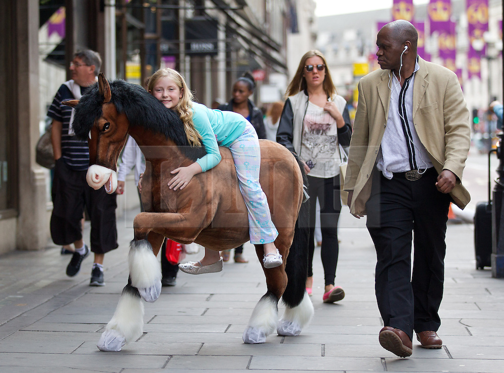 © Licensed to London News Pictures. 27/06/2013. London, UK. Teagan, 9, is seen on Regents Street with a 'Clydesdale Prancing Pony' (Hamleys price GB£850) at the Christmas in June press event at Hamleys toy shop in London today (27/06/2013).  Held in retailers world famous Regents Street store, the event showcases the predicted top toys for Christmas 2013. Photo credit: Matt Cetti-Roberts/LNP