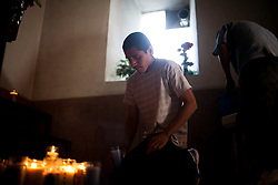 Migrants pray for safe passage at the Our Lady of Guadalupe Church in Altar, Sonora, before beginning their trip across the desert and into the US.  Altar is the starting point for many migrants' journeys to the US. In Altar they find guides and coyotes to take them across the border.  The town's economy is nearly entirely dependent on the migrants. Recently drug cartels have become involced in the smuggling of people, using the same routes as the drugs and charging the migrants an exit tax to leave the country.
