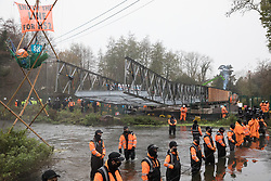 Denham, UK. 8th December, 2020. HS2 security guards form a line across the River Colne in front of Dan Hooper, widely known as Swampy during the 1990s. The climate and roads activist had occupied a bamboo tripod the previous day in order to delay the building of a bridge as part of works for the controversial HS2 high-speed rail link and a large security operation involving officers from at least three police forces, the National Eviction Team and HS2 security guards was put in place to facilitate his removal.