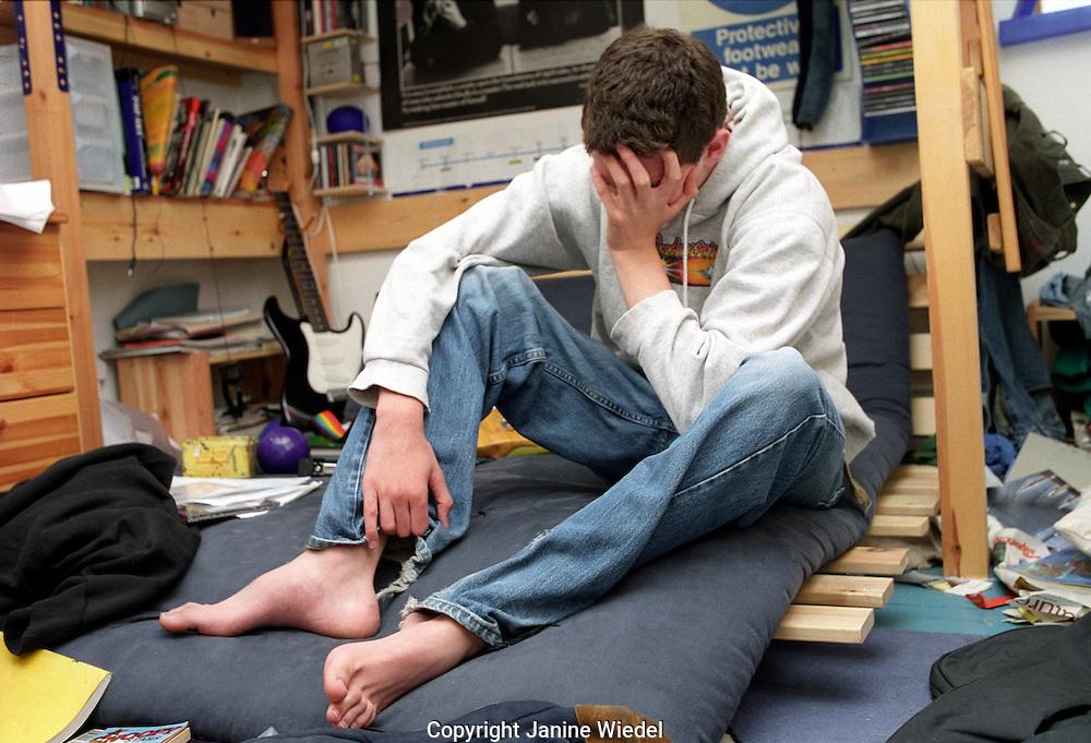 depressed teenaged boy alone in his bedroom
