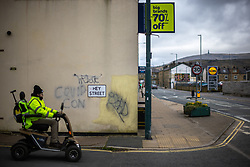 """© Licensed to London News Pictures . 19/03/2021. Todmorden , UK . Graffiti reading """" COVID CON """" is seen on a rendered wall opposite a branch of Lidl at the junction of Hey Street and Halifax Road . Exploring a year of experiences , lessons and consequences of Coronavirus in the NW of England . Photo credit : Joel Goodman/LNP"""