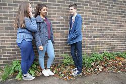 Teenage girls talking to teenage boy  leaning on wall