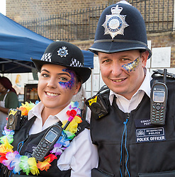 London, August 28 2017. Police officers sport garlands and glitter face paint on Day Two of the Notting Hill Carnival, Europe's biggest street party held over two days of the August bank holiday weekend, attracting over a million people. © Paul Davey.