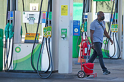 © Licensed to London News Pictures 24/09/2021.<br /> Mottingham, UK, A man walking across closed forecourt wearing a covid mask is going to buy food not fuel, No petrol or Diesel at this BP station in Mottingham Village, South East London. Chaos at the forecourts as people start to panic buy petrol. BP has started to ration petrol and diesel due to a shortage of truckers. Photo credit:Grant Falvey/LNP