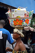 A Malian woman walks around the marketplace in Bamako, Mali selling school textbooks and journals that she carries on her head in a brightly decorated metal bowl.