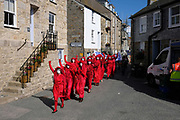 Climate change Red Rebels activists from the seaside town of St Ives in Cornwall gathered to protest at the lack of activity by the British Government on climate change on 31st August 2019, in St Ives, United Kingdom. The group, including the spectacularly costumed Red Rebels lead a procession of Extinction Rebellion activists through the town of St Ives, United Kingdom. The group protested about rising sea levels caused by climate breakdown. The Red Rebells performance artivist troupe dedicated to illuminating the global environmental crisis and supporting groups and organisations fighting to save humanity and all species from mass extinction. Extinction Rebellion is a climate change group started in 2018 and has gained a huge following of people committed to peaceful protests. These protests are highlighting that the government is not doing enough to avoid catastrophic climate change and to demand the government take radical action to save the planet.