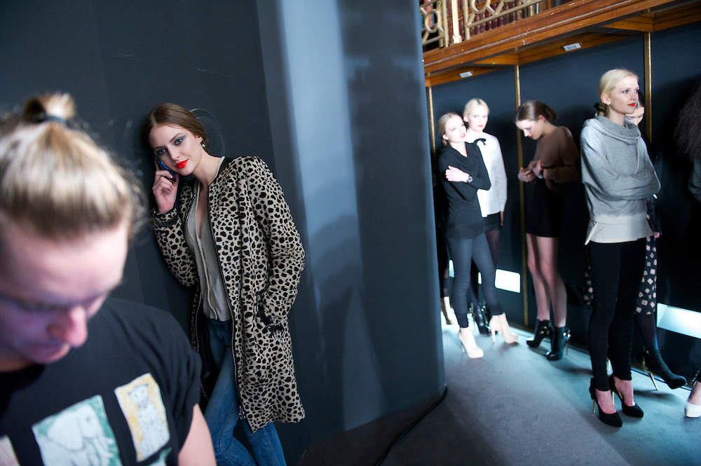 A model answers a phone call before particiating in a walk through before the Temperley autumn 2011 collection at The British Museum in London on 20 February 2011.
