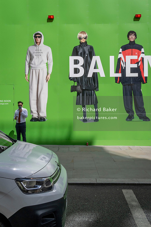 A man uses his phone beneath the temporary construction hoarding for Balenciaga, a retail space which is opening soon on Bond Street, on 27th April 2021, in London, England. Balenciaga is a fashion house founded in 1917 by Spanish designer Cristóbal Balenciaga in San Sebastián, Spain.