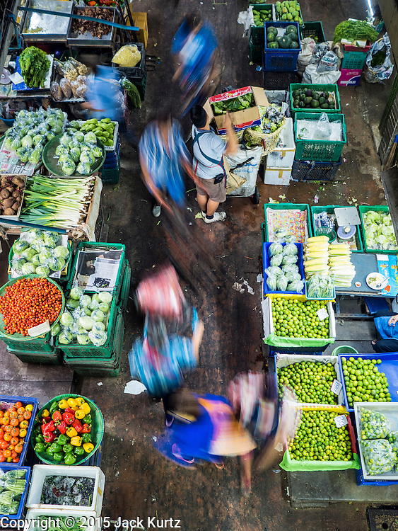 """21 DECEMBER 2015 - BANGKOK, THAILAND:  People walk through the produce section of Pak Khlong Talat, also called the Flower Market. The market has been a Bangkok landmark for more than 50 years and is the largest wholesale flower market in Bangkok. A recent renovation resulted in many stalls being closed to make room for chain restaurants to attract tourists. Now Bangkok city officials are threatening to evict sidewalk vendors who line the outside of the market. Evicting the sidewalk vendors is a part of a citywide effort to """"clean up"""" Bangkok.      PHOTO BY JACK KURTZ"""