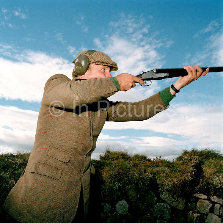 "A 'gun' grouse shooting in Nidderdale, North Yorkshire, UK. Driven grouse shooting is a field sport of the UK, popular because it provides a challenge due to the rapid flight of the grouse. The grouse shooting season extends from 12 August, often called the ""Glorious Twelfth"", to 10 December each year. The name 'driven grouse shooting' refers to the way in which the grouse are driven towards the hunters (termed 'guns') by beaters. A shooting party usually includes 8-10 guns who stand in a line in the butts - hides for shooting spaced some 20-30 m apart, screened by a turf or stone wall and usually sunken into the ground to minimise their profile - to shoot the grouse in flight."