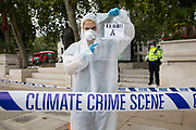 Extinction Rebellion 'crime scene investigators' in white suits and masks put up climate crime scene tape to investigate areas of ecocide in a performance in Parliament Square in an area already cordoned off on 7th September 2020 in London, United Kingdom. The 20 investigators were protesting at the UK government's ecocide along the HS2 route. Extinction Rebellion is a climate change group started in 2018 and has gained a huge following of people committed to peaceful protests. These protests are highlighting that the government is not doing enough to avoid catastrophic climate change and to demand the government take radical action to save the planet.