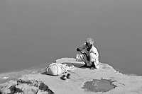 """India, Khajuraho,1999. A """"dhobi wallah,"""" or laundry man, takes a moment to eat before performing a daily miracle - clean white clothes from less than clean conditions."""
