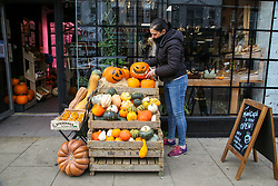 © Licensed to London News Pictures. 12/10/2020. London, UK. A woman adds a carved pumpkin to the display of pumpkins outside Mum's Cafe in north London as it prepares for Halloween. The government has announced that trick-and-treating will not be allowed in areas under local lockdown.   <br /> At 3.30pm Prime Minister Boris Johnson will address the House of Commons followed by an address to the public on TV at 6pm where he will outline the three-tier plan with areas in England labelled as medium, high or very high risk, and this will inform the 'appropriate interventions' needed in each area. Photo credit: Dinendra Haria/LNP