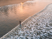 Aerial view of a woman doing yoga in the ocean during sunrise on Palolem beach, Goa, India.
